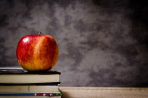 Insurance for Private Schools Florida - red apple sitting on stack of books