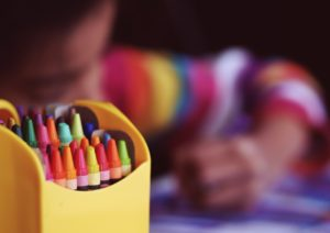 Charter School Insurance Florida - assorted crayons in focus with child using crayons out of focus in background