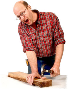 Florida Workers Compensation Insurance - male worker yells in pain after hitting thumb with hammer