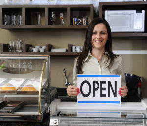 Florida Business Insurance - Female small business owner holding up an Open sign