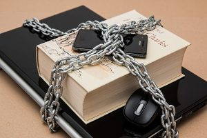 Cyber Liability Coverage South Carolina - laptop, mouse, book, and phone tied up in chains